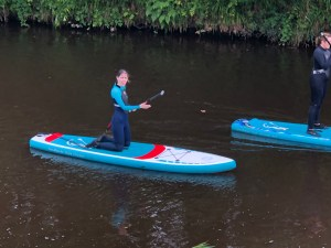 Woma, wearing a black and blue wetsuit, kneeling on a paddleboard on a river, she is smiling