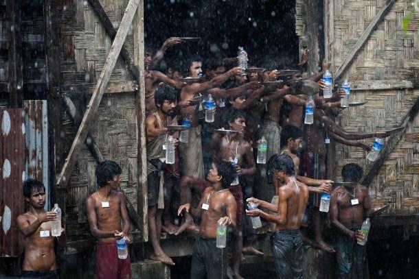 Un grupo de inmigrantes rescatados de un bote llena sus botellas con agua de lluvia en Birmania. AFP - Ye Aung Thu.