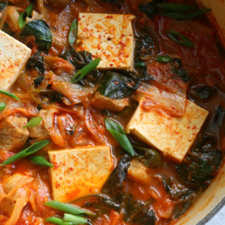 Kimchi Jjigae - spicy, savory classic Korean soup recipe made with tender pork shoulder and fermented kimchi. This easy soup has big flavor!