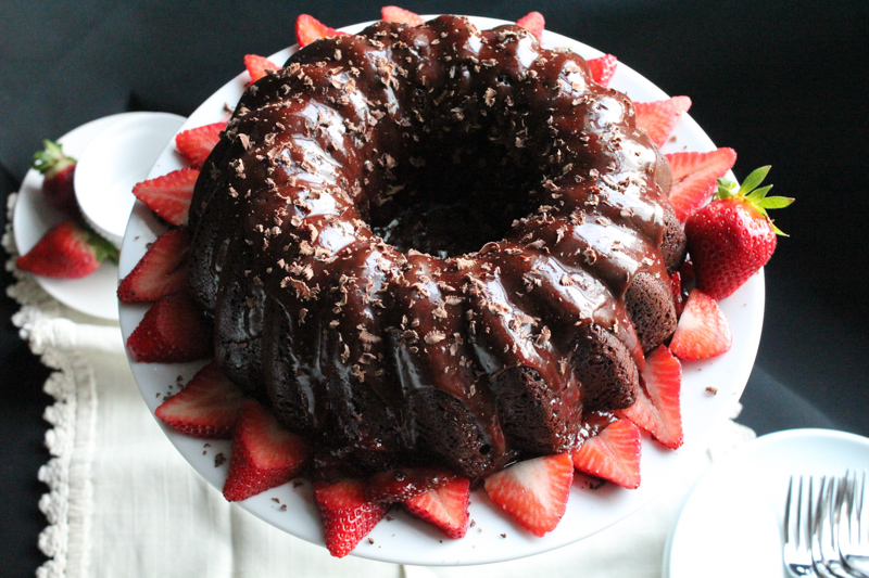 Triple Chocolate Bundt Cake smothered in chocolate ganache and balsamic strawberry sauce. This is the ultimate chocolate lover's dessert.
