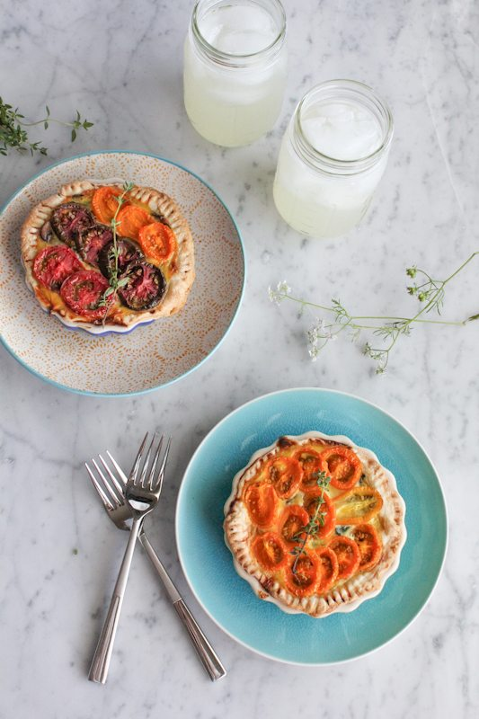 Two plates of Heirloom tomato tarts, two forks, and two glass jars with beverages.