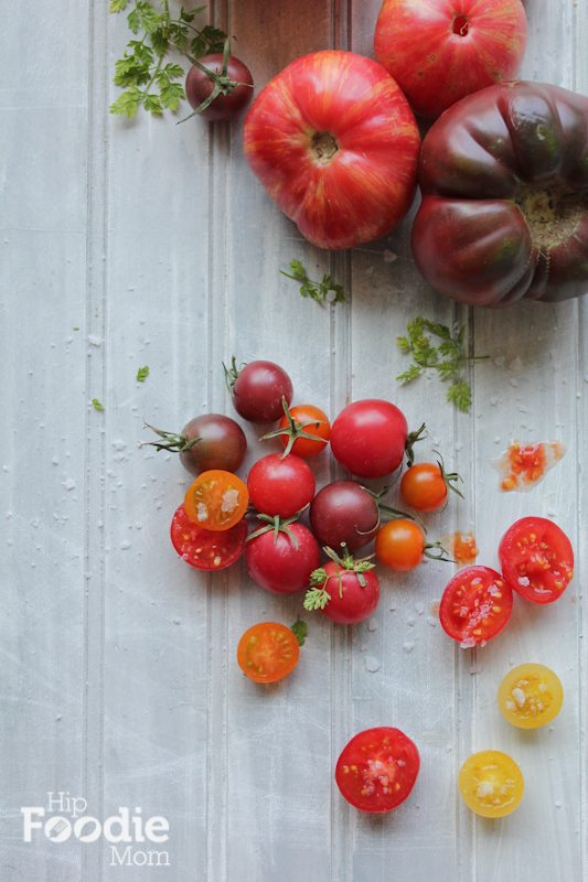 Heirloom tomatoes on a white wood surface.