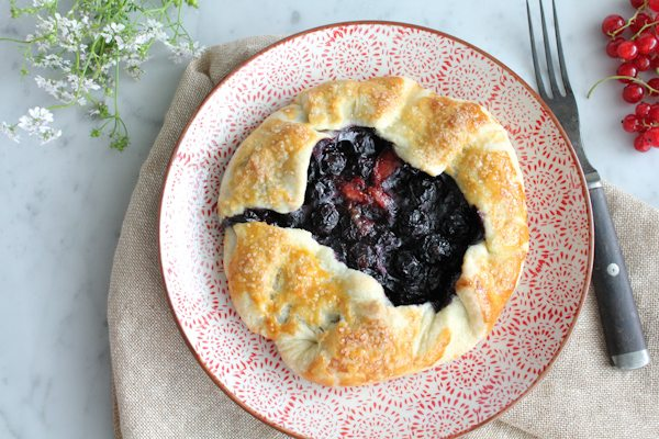 A mini berry galette on a plate with a napkin, berries, and flowers.