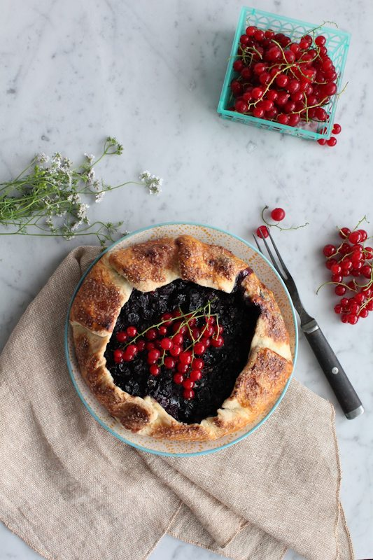 A mini berry galette on a plate with a basket of berries, and flowers.