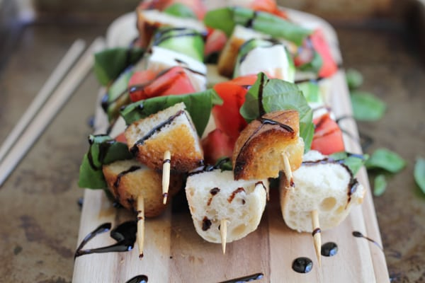 A stack of Caprese kabobs on a wood cutting board.