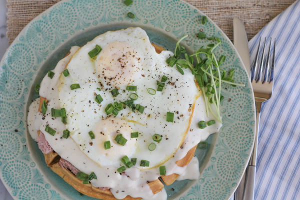 Whole wheat waffle topped with ham, tons of gruyere cheese, a luscious béchamel sauce, and topped with two fried eggs! This is a Croque Madame Waffle!!! #brunch #croquemadame