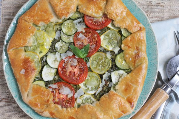 Summer Vegetable Galette with Pesto on a plate with a napkin and silverware.