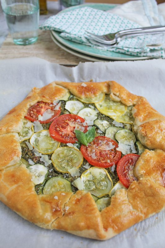 Summer Vegetable Galette with Pesto on a piece of parchment paper with plates, napkins, and silverware in the background.