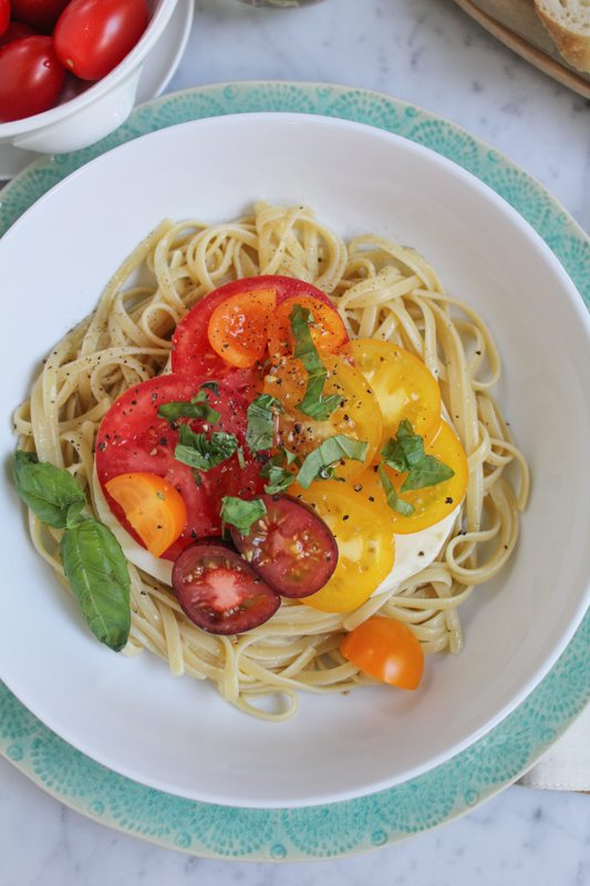 A bowl of Summer Caprese pasta salad with a small white bowl of tomatoes.