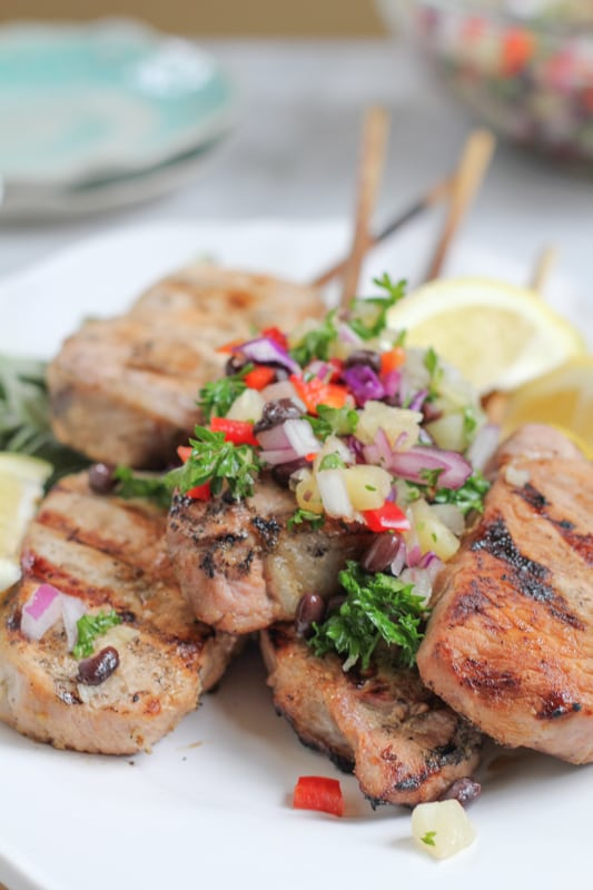 Grilled Pork Chops On a Stick With Pineapple Salsa on a plate.