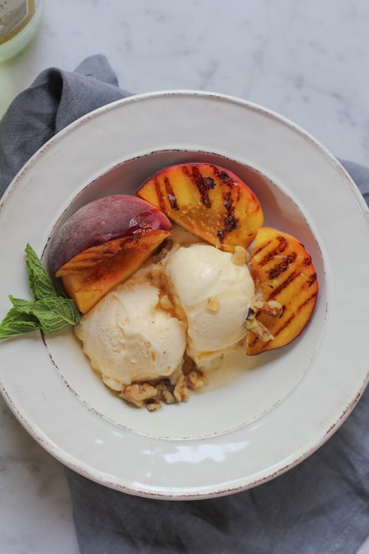 Vanilla Ice Cream with Grilled Peaches in a white bowl, with a gray napkin.