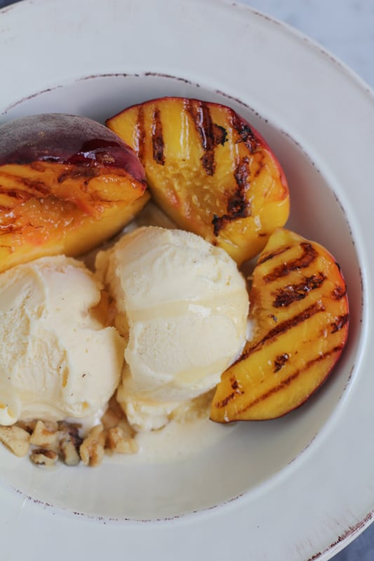 Vanilla ice cream with grilled peaches in a white bowl.