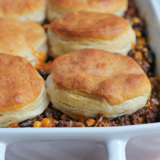 Mexican Biscuit Casserole! Change up taco night!! Seasoned ground beef with black beans and beef, topped with big flaky buttermilk biscuits!