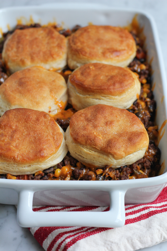 Change up taco night with this Mexican Biscuit Casserole! Taco seasoned ground beef with black beans and beef, topped with big flaky buttermilk biscuits!