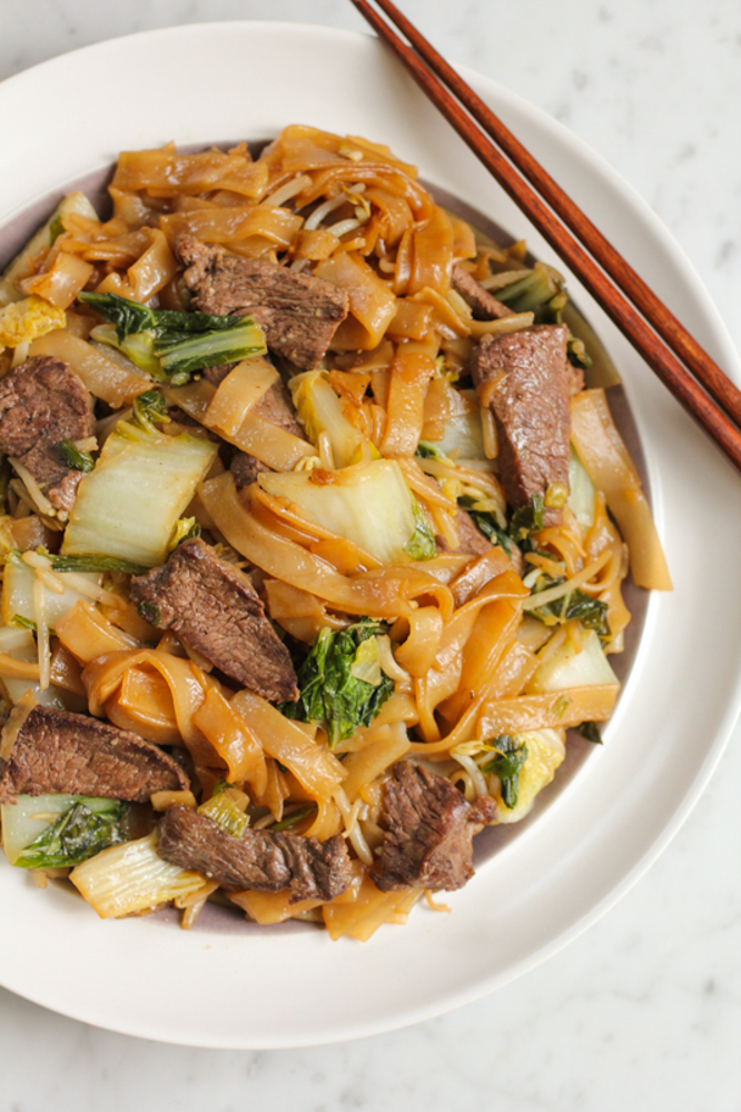 chow fun noodles with boneless beef short ribs on white plate with chopsticks