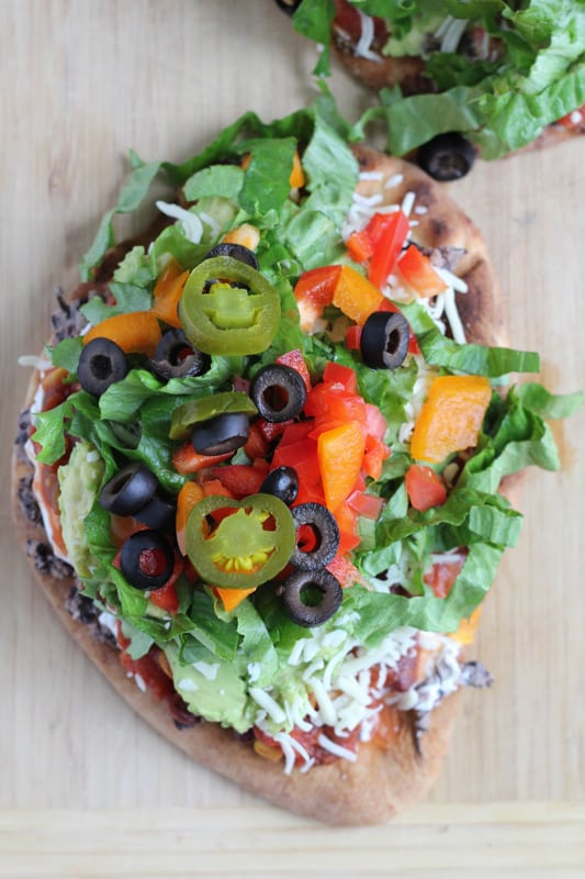 7 Layer Dip Flatbreads on a wood surface.