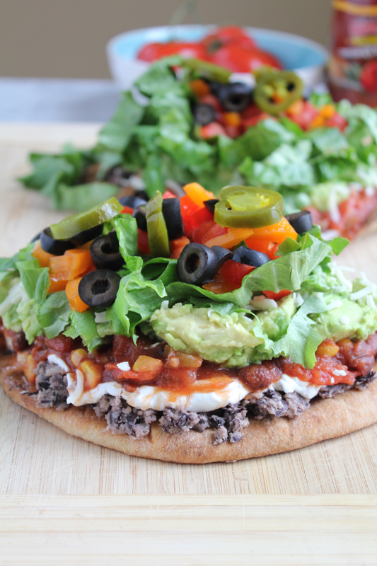 7 Layer Dip Flatbreads on a wood cutting board.