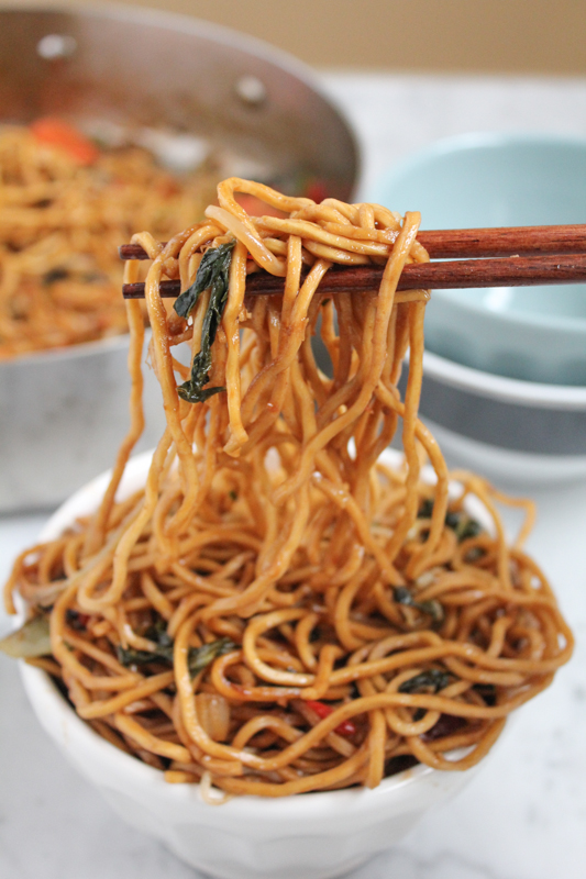 using chopsticks to remove Asian noodles from a bowl