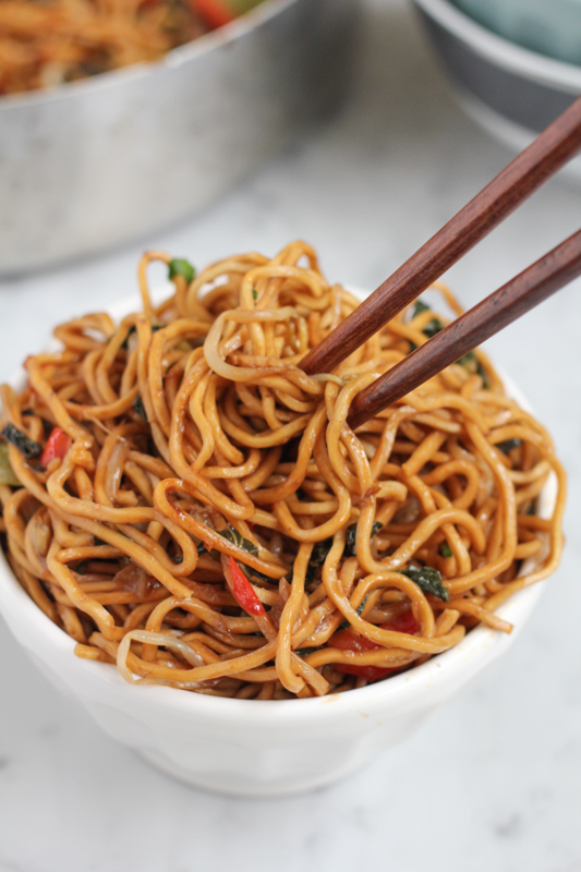 bowl of vegetable chow mein being eaten with chopsticks