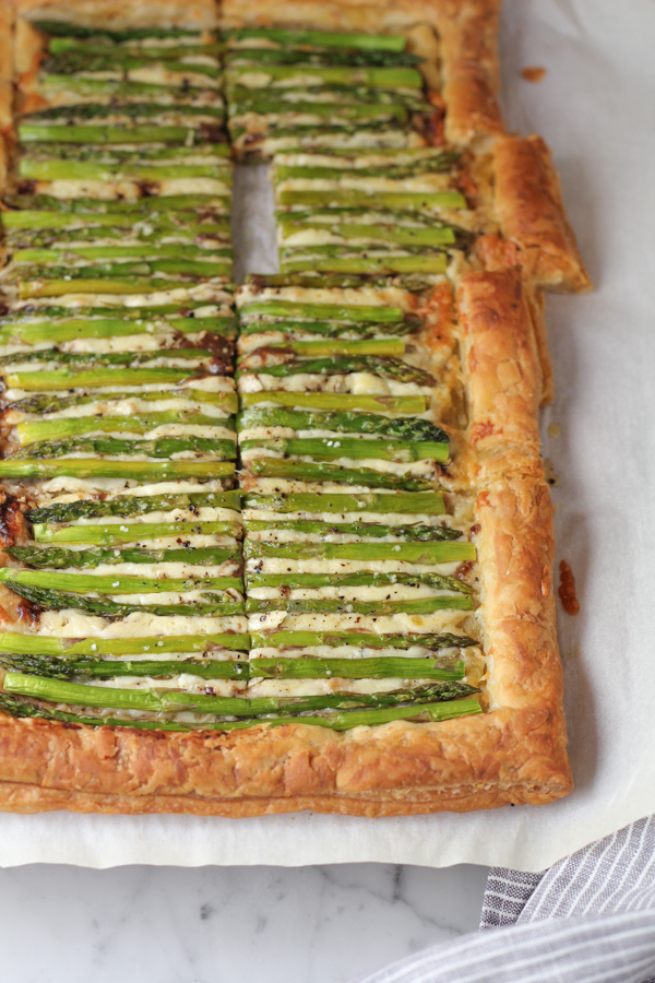 Sliced Asparagus Gruyere Tart on parchment paper.