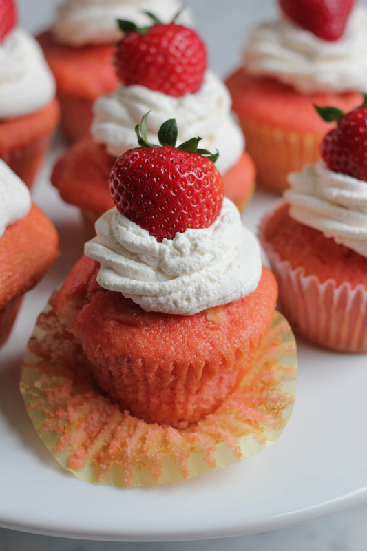 Classic Strawberry Cupcakes with fresh whipped cream and topped with a strawberry. These cupcakes are made purely from scratch with real strawberries. Fluffy, moist, and exploding with strawberry flavor! #CookfortheCure @kitchenaidusa