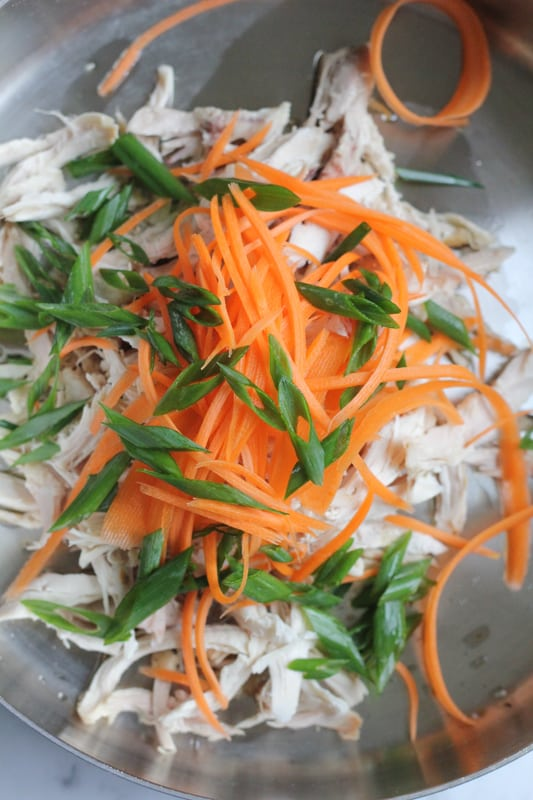 Chicken, carrots, and spring onions in a bowl for Chinese chicken salad.