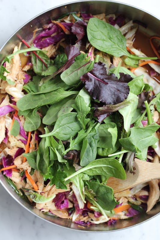 Chinese chicken salad in a mixing bowl topped with greens.