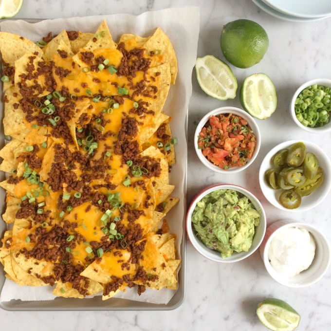 Beef nachos in a sheet pan with bowls of toppings.