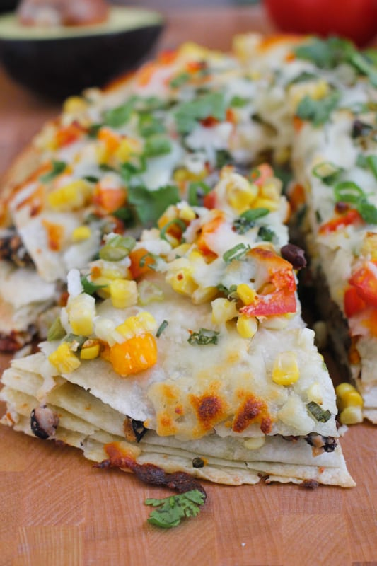 Close up photo of a sliced Corn and Black Bean Tortilla Tart on a wood cutting board.