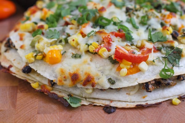 Corn and Black Bean Tortilla Tart on a wood cutting board.