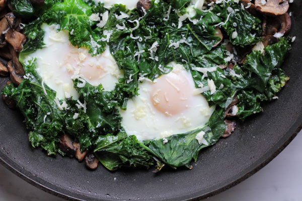 Fried eggs with sautéed kale and mushrooms. So flavorful and delicious! This is savory brunch at its best! And SO easy to make! #brunchweek