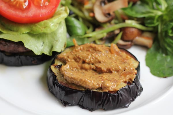 A slice of eggplant with mustard for Grilled Eggplant Bun Burgers.