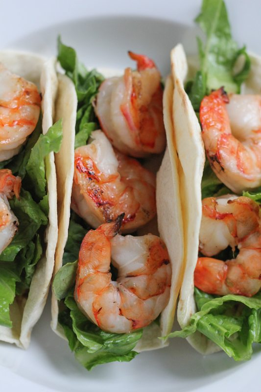 Grilled Shrimp Tacos with Mexican Crema on a white plate.