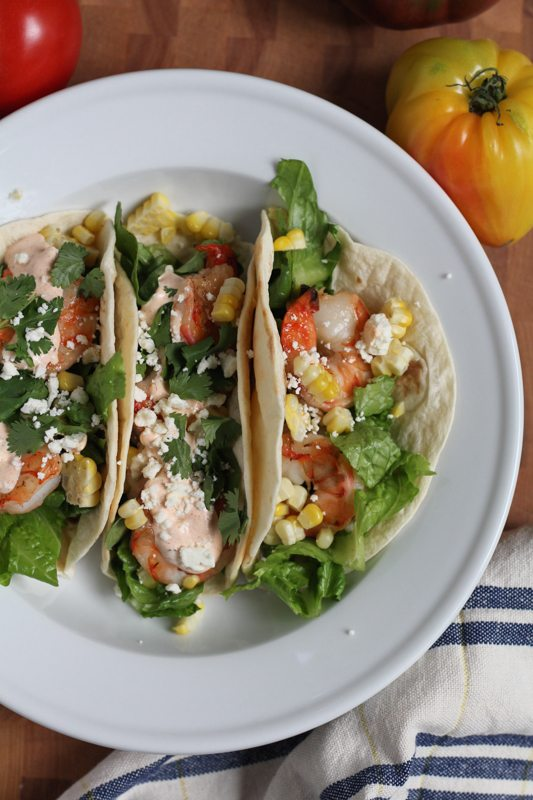 Grilled Shrimp Tacos with Mexican Crema on a white plate with a napkin and tomatoes.