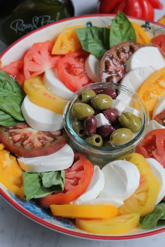 Photo of a platter of Simple Caprese Salad with a bowl of olives and feta in the center.