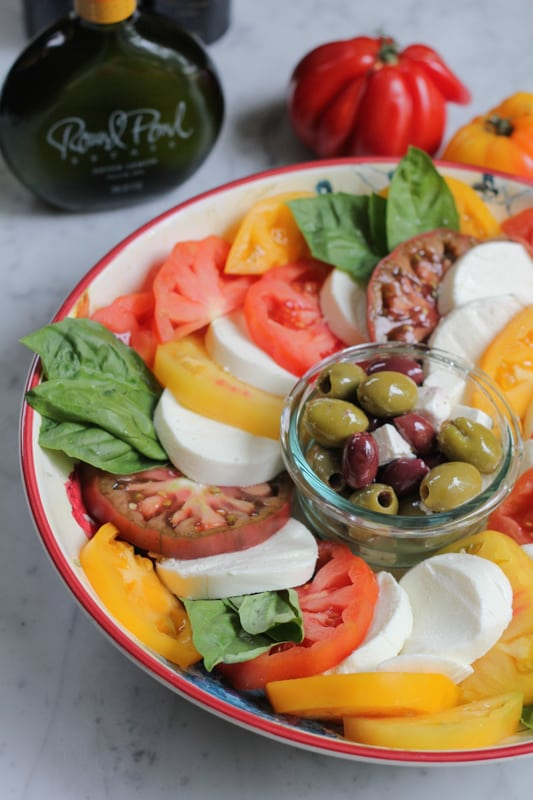 A platter of Simple Caprese Salad with a bowl of olives and feta, and a bottle of olive oil and tomatos in the background.