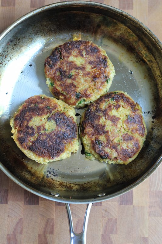 Three chickpea burgers in a skillet.