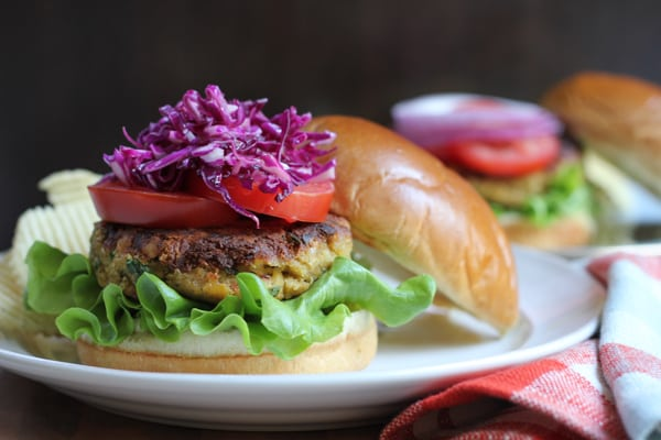 A chickpea burger topped with tomatoes and red cabbage slaw on a plate.