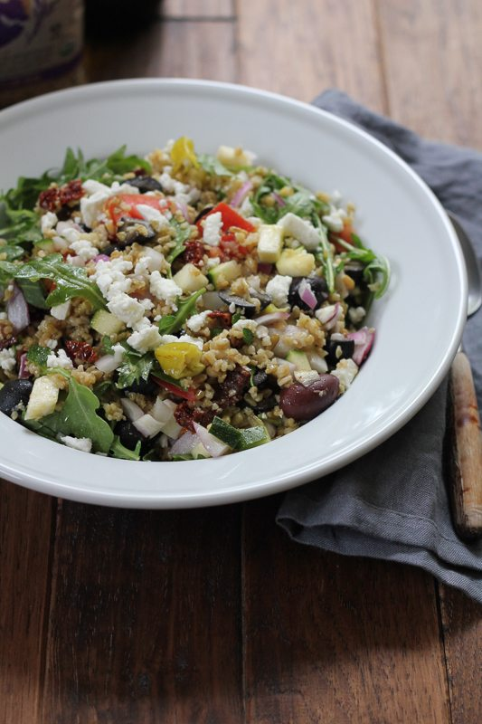 A bowl of Mediterranean Freekeh Salad in a white bowl on a wood surface.