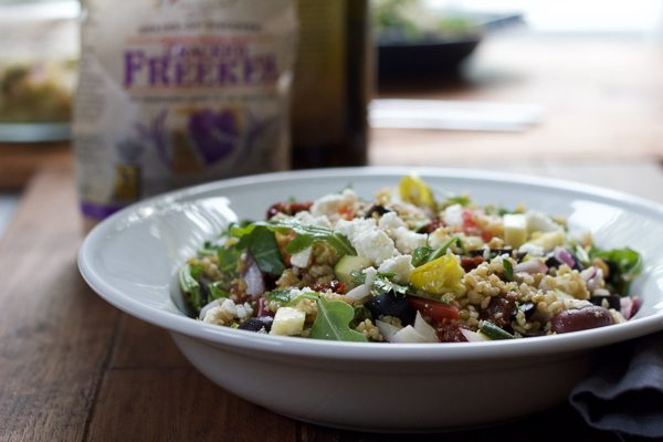 A bowl of Mediterranean Freekeh Salad with a bag of freekeh grains in the background.