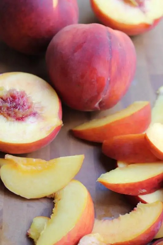 Peaches and slices of peaches for Olive Oil Honey Cake With Fresh Peaches.