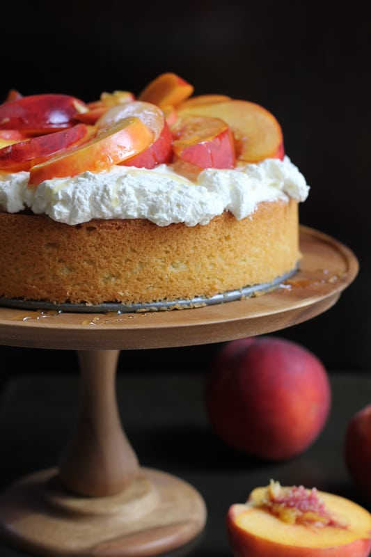 Olive Oil Honey Cake With Fresh Peaches on a wooden cake stand, surrounded by peaches.