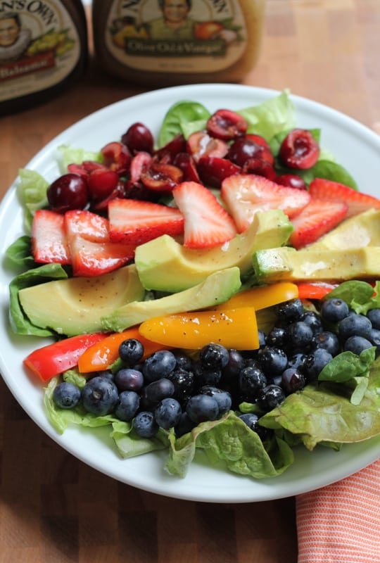 A plate of Summer Berry Salad with bottles of vinaigrette in the background.