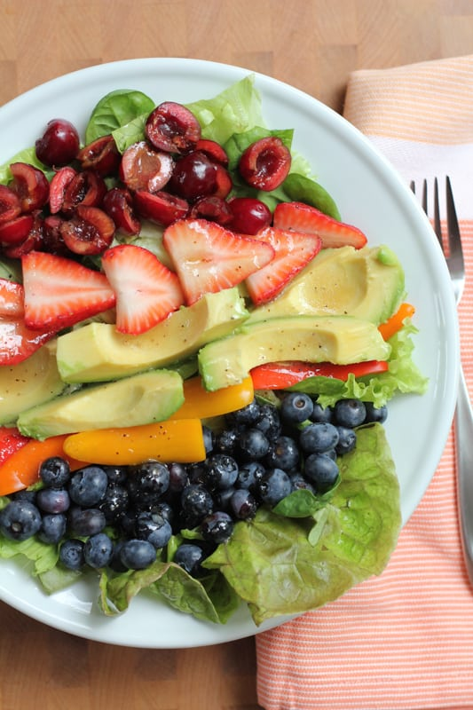 Overhead photo of a plate of Summer Berry Salad with a napkin and a fork.