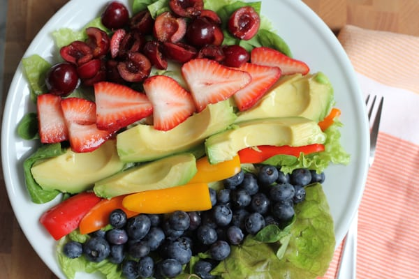 Summer Berry Salad on a plate with a napkin and fork.