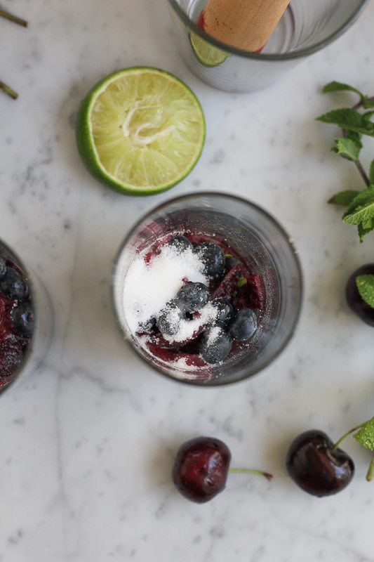 Blueberries and sugar at the bottom of a glass with half a lime, mint sprigs, and cherries.