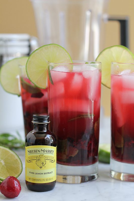 A bottle of lemon extract with glasses of blueberry cherry mojitos.