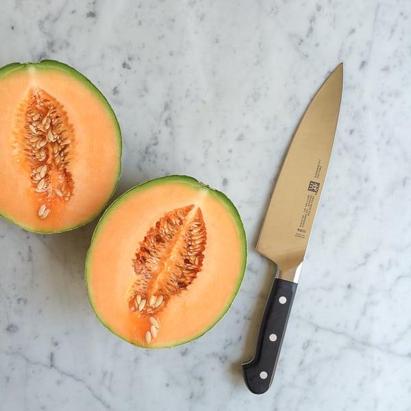 A cantaloupe sliced in half for Simple Cantaloupe Salad and a knife.