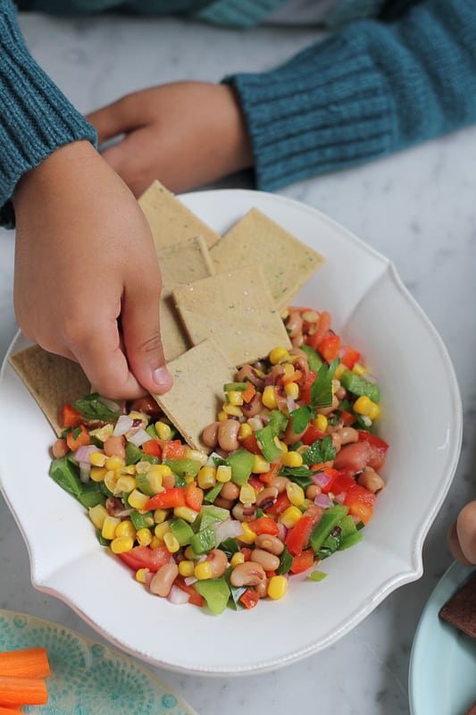 Crackers being dipped into a bowl of Texas Caviar.