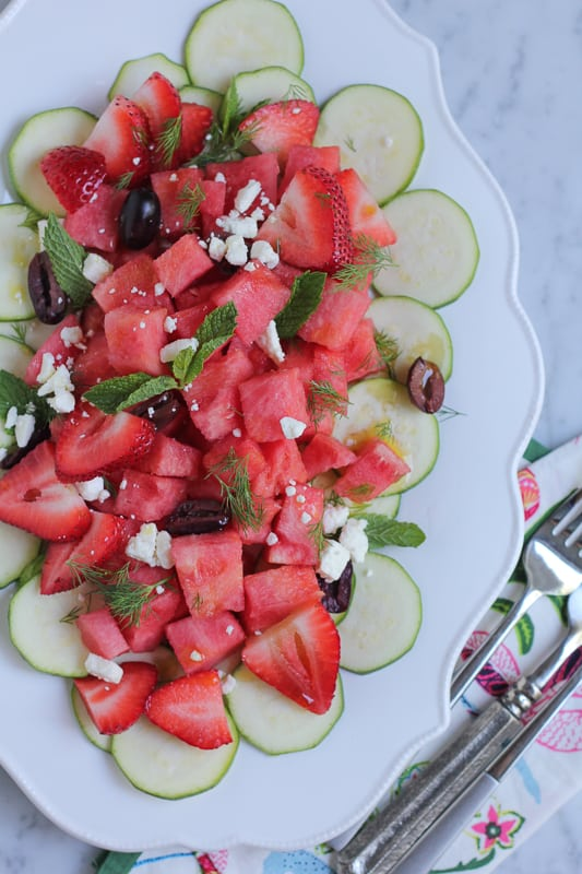 Zucchini watermelon and feta salad on a white plate with a napkin and silverware.